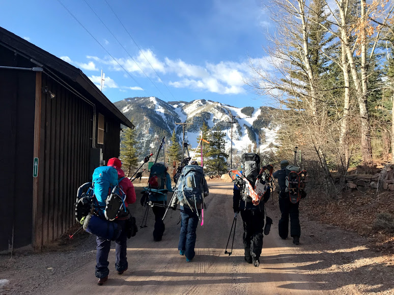 A group walks towards mountains on a dirt road carrying backcountry ski and snowshoe equipment