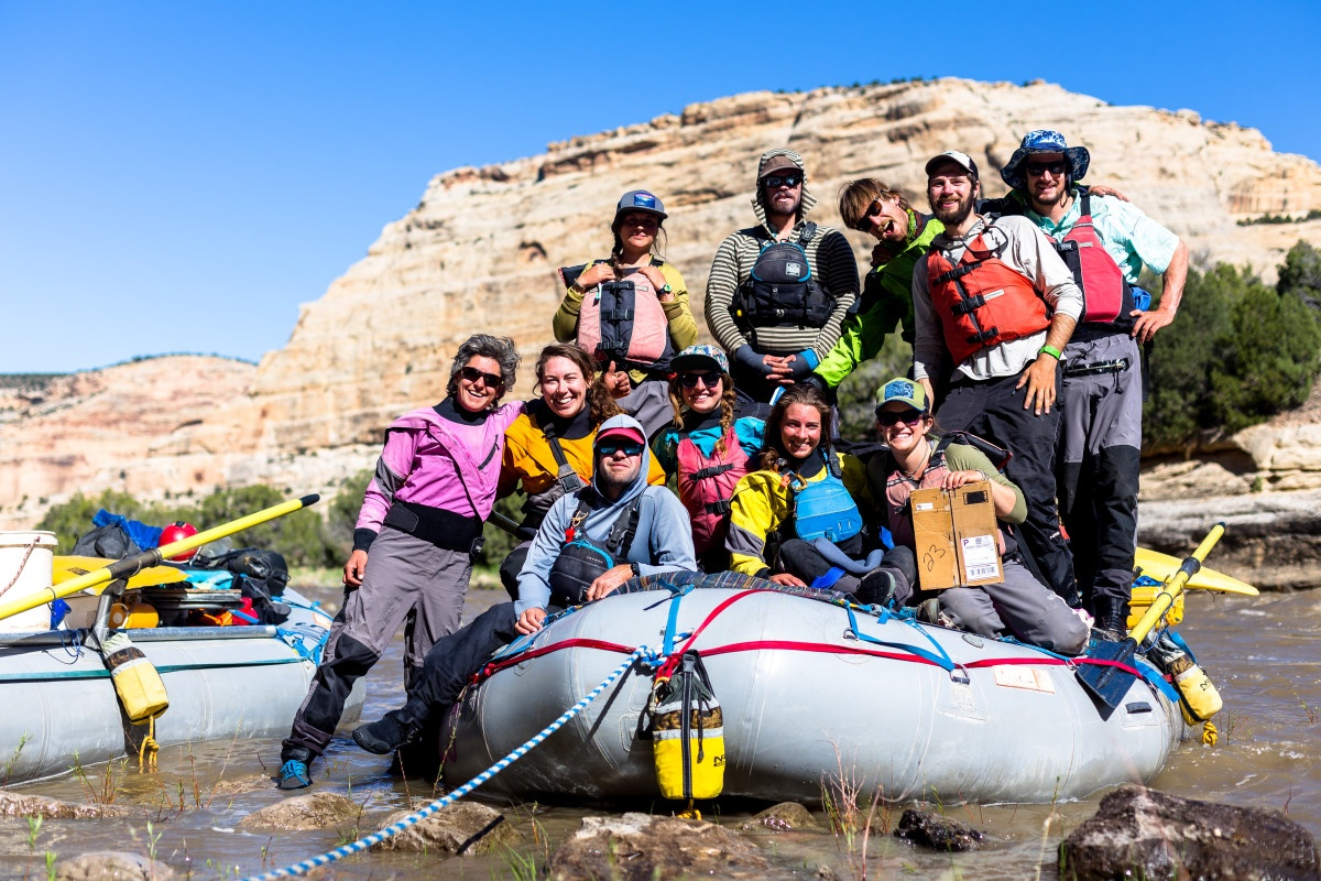 Smiling people pose for a group shot wearing river gear on a rafting expedition