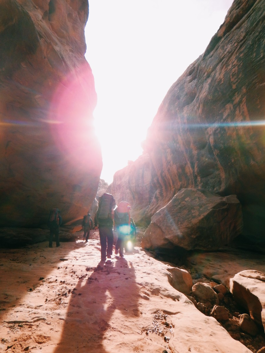 Figures walk away from camera into the sun in the canyonlands