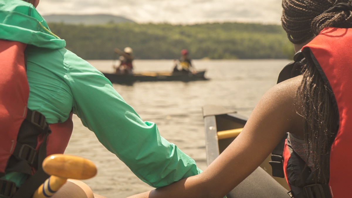 Two teen girls hold onto each other's canoe