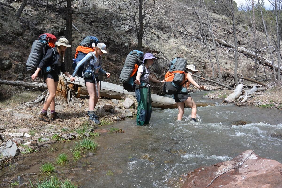 Four girls wearing backpacks help each other cross a creek