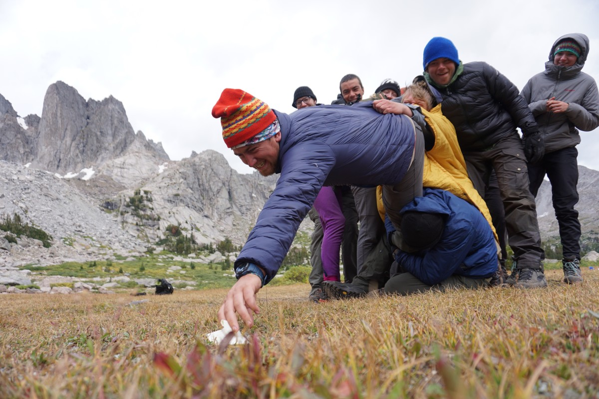 Group of people holding onto a person reaching to grab an object off the ground while team building in the mountains
