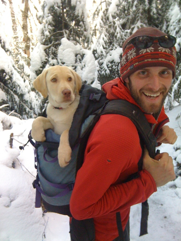 Smiling man wearing red fleece and hat carries yellow lab puppy in a backpack