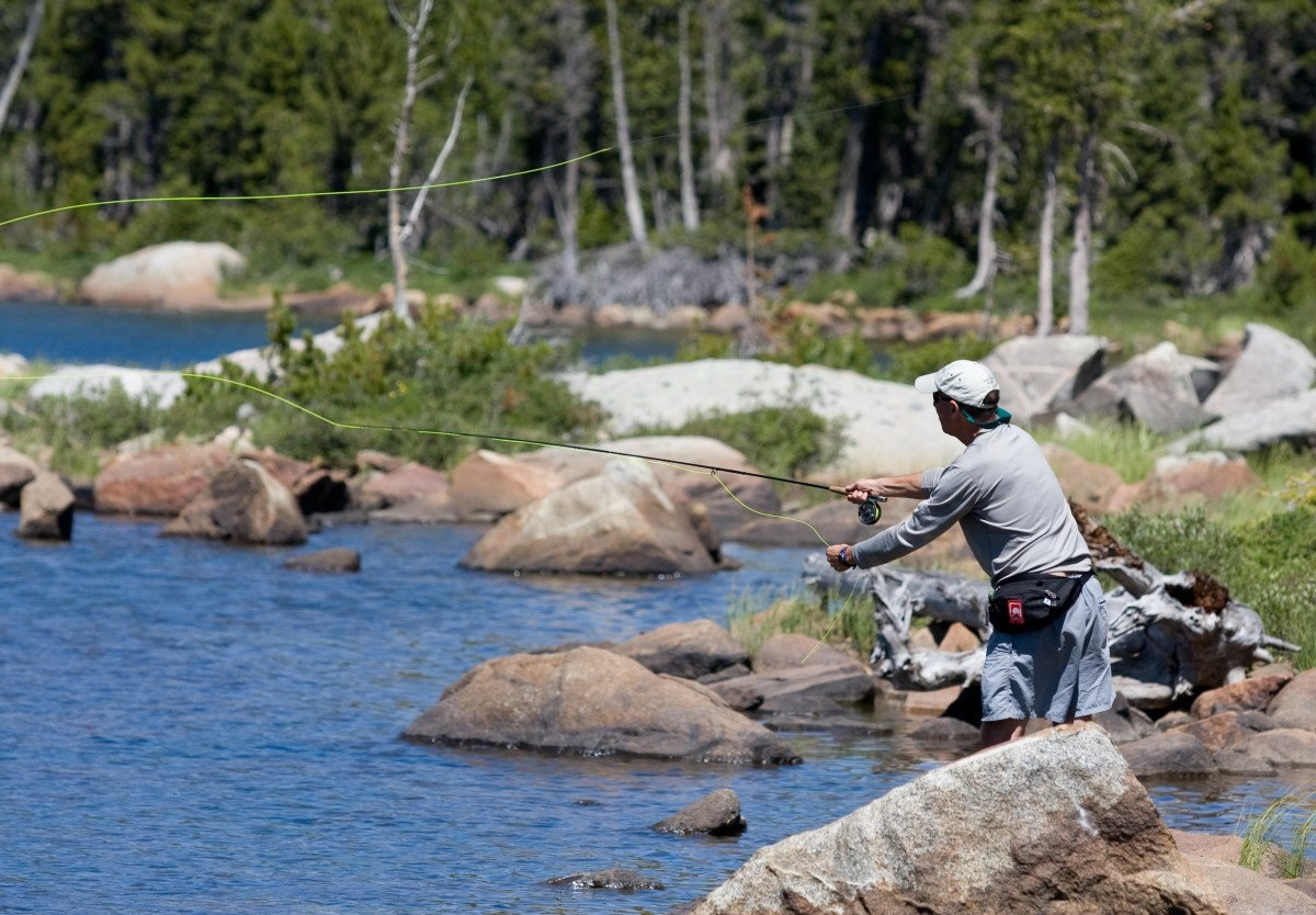 Man wearing baseball cap fly fishes at the rocky edge of a blue lake in Wyoming's mountains