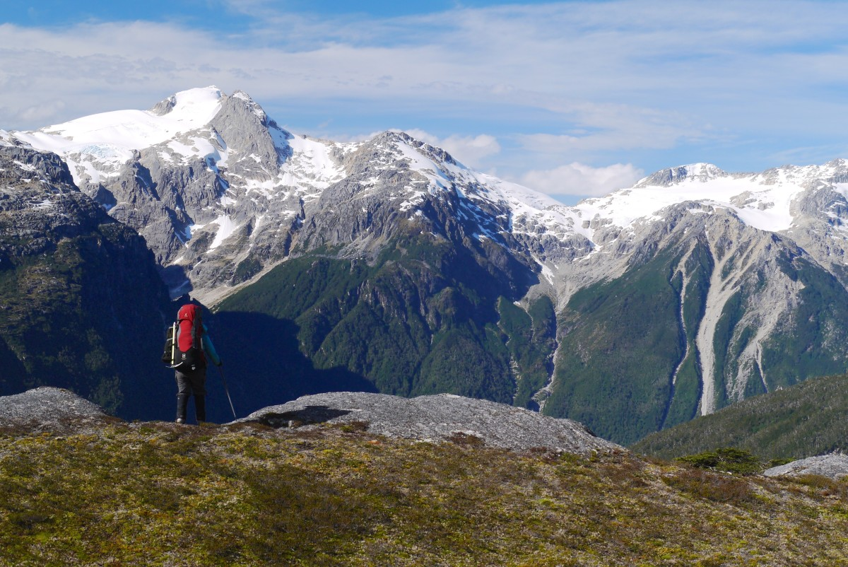A backpacker pauses on top of the ridge with snowy peaks in the distance