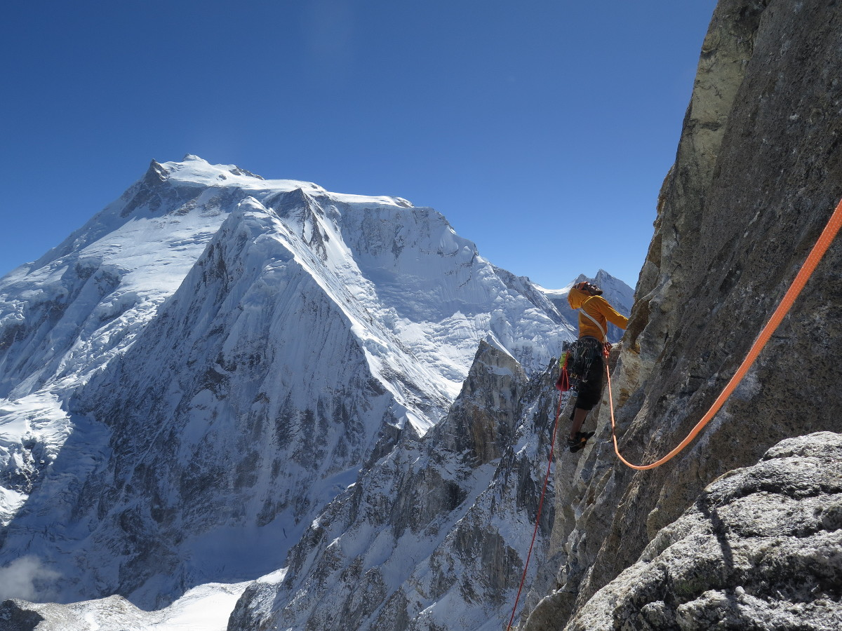 rock climber in a harness on a steep face surrounded by snowy high-altitude peaks