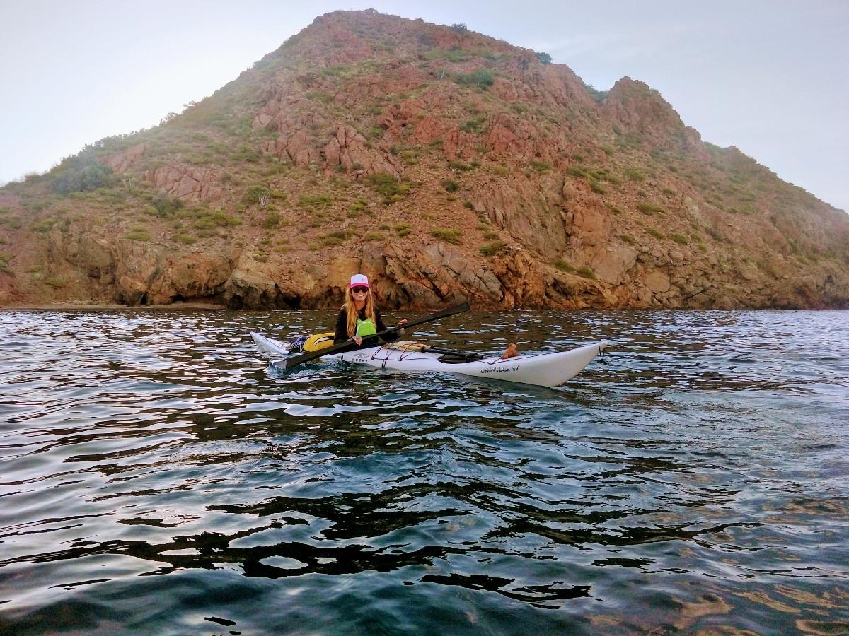 woman wearing baseball cap paddles white kayak near shoreline with steep rocky hill