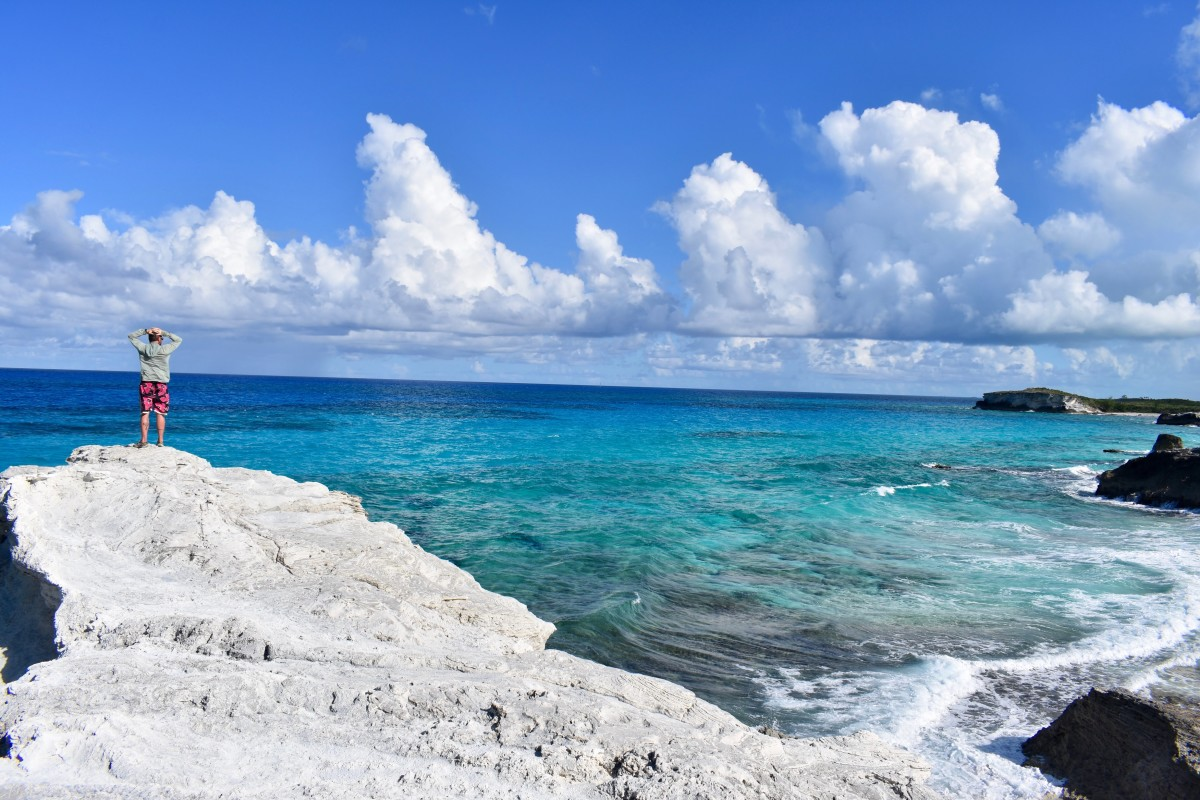 NOLS student stands on a rocky outcrop on the shore of the turquoise blue ocean in the Caribbean
