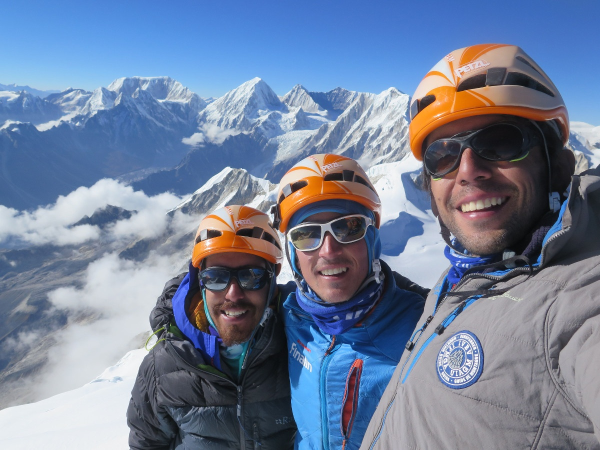 three smiling climbers wearing orange and white helmets at the summit of a mountain with snowy peaks beyond