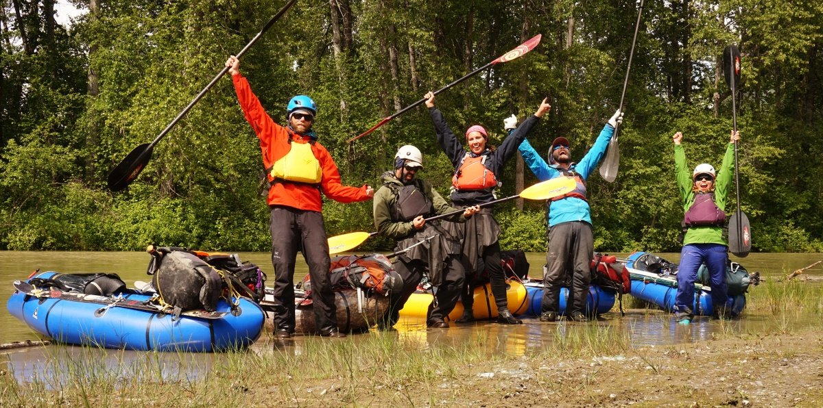 Five smiling instructors wearing kayaking gear fling their arms out, holding their paddles triumphantly