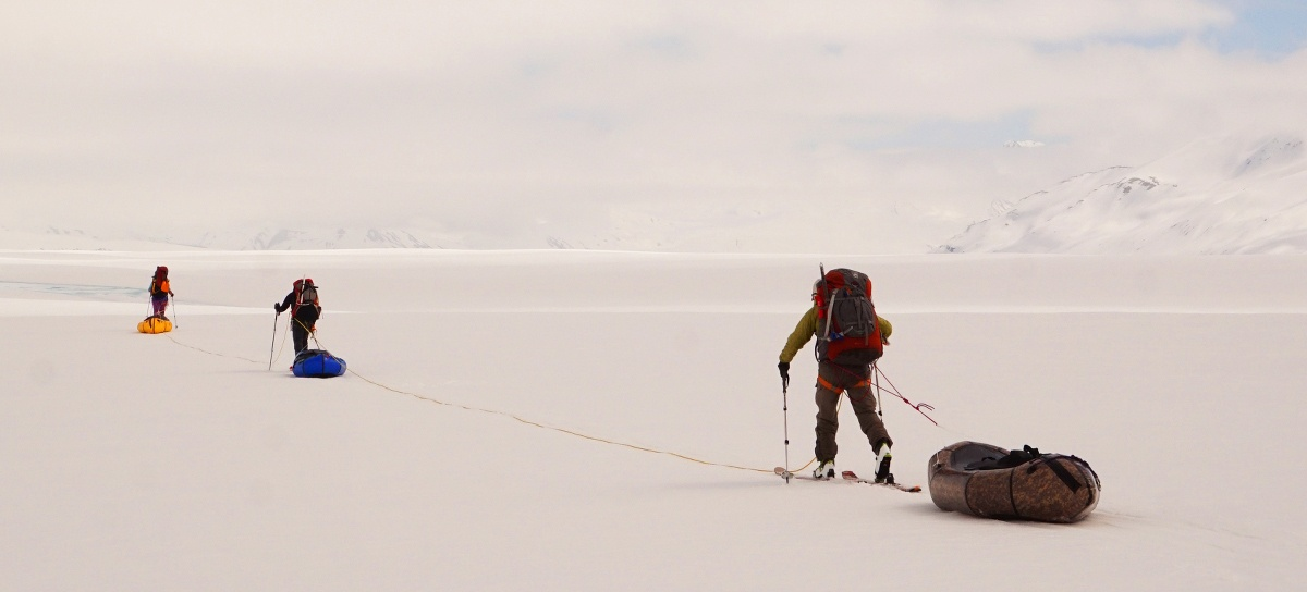Team of three walk across a snow flat using trekking poles and dragging their packrafts like sleds
