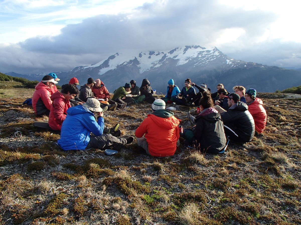 Group of NOLS students have a discussion sitting in a circle