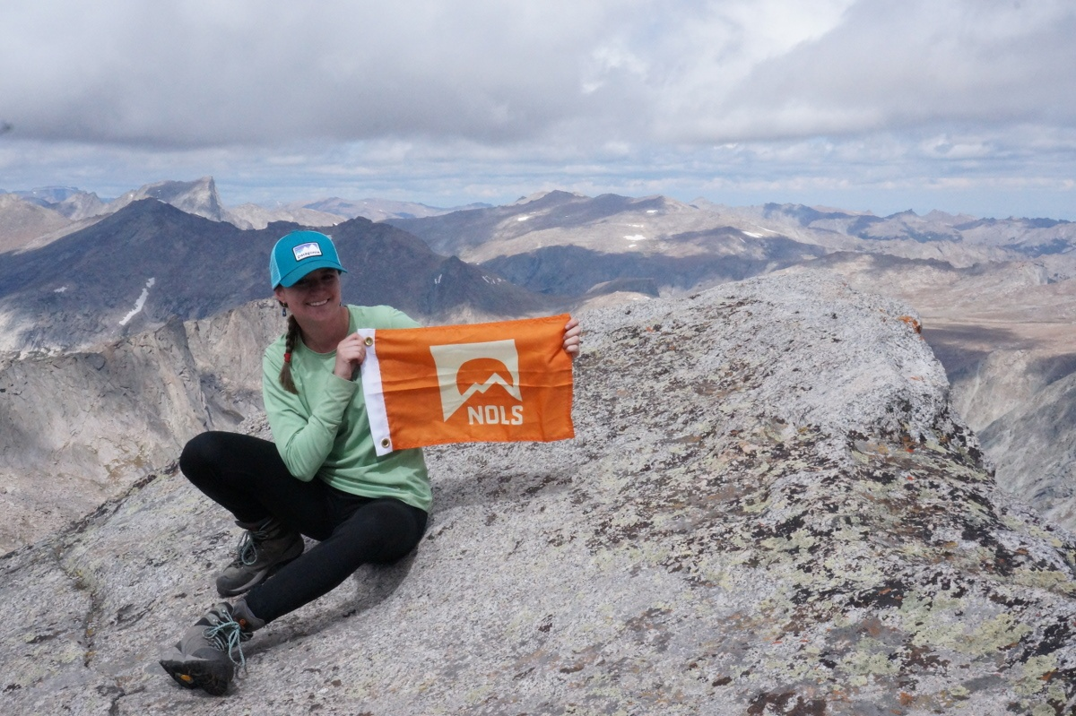Maddy smiling and holding an orange NOLS summit flag on a peak in the mountains