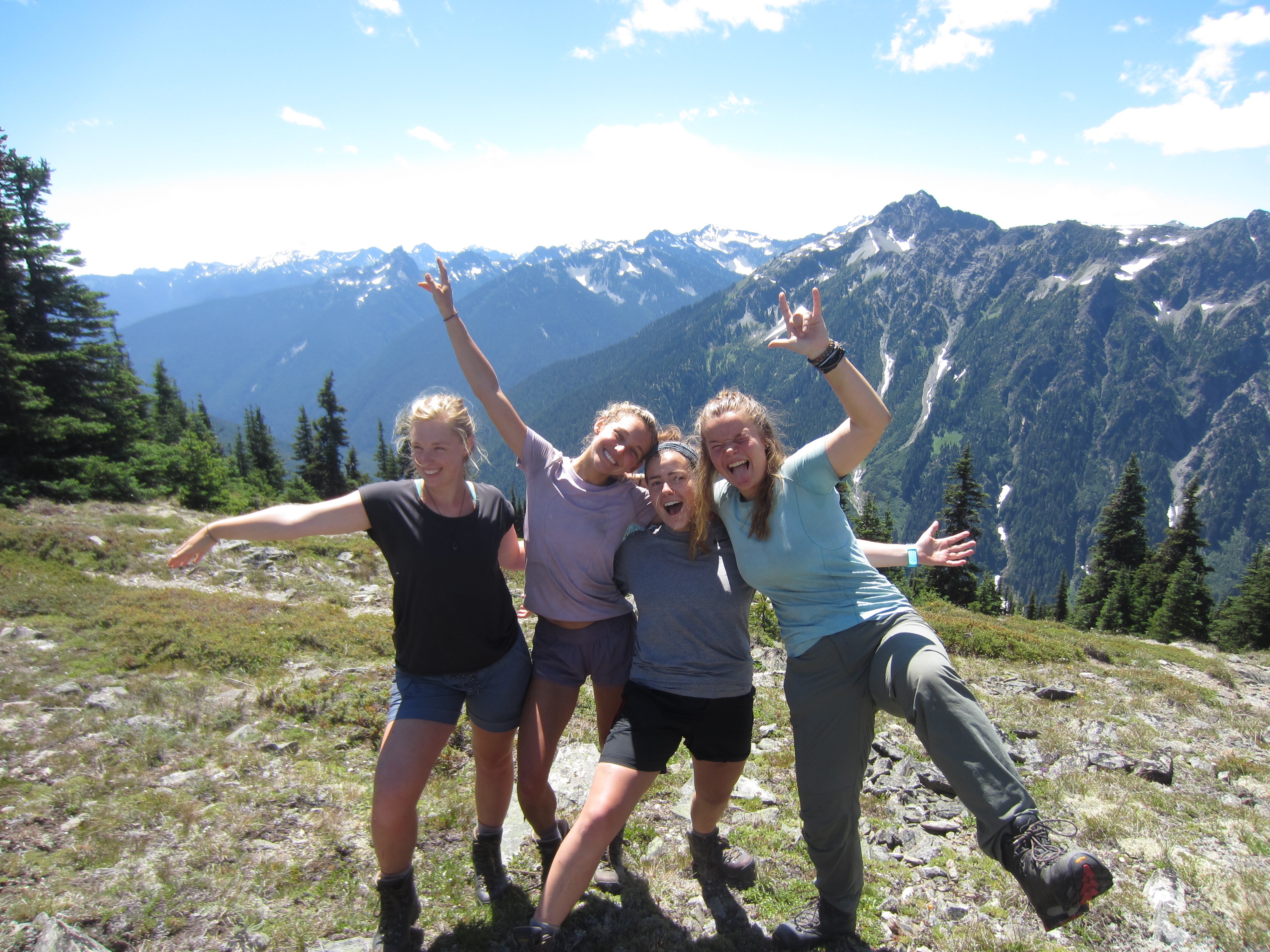 four NOLS students smile and celebrate reaching the top of Grey Wolf Pass in the Pacific Northwest together