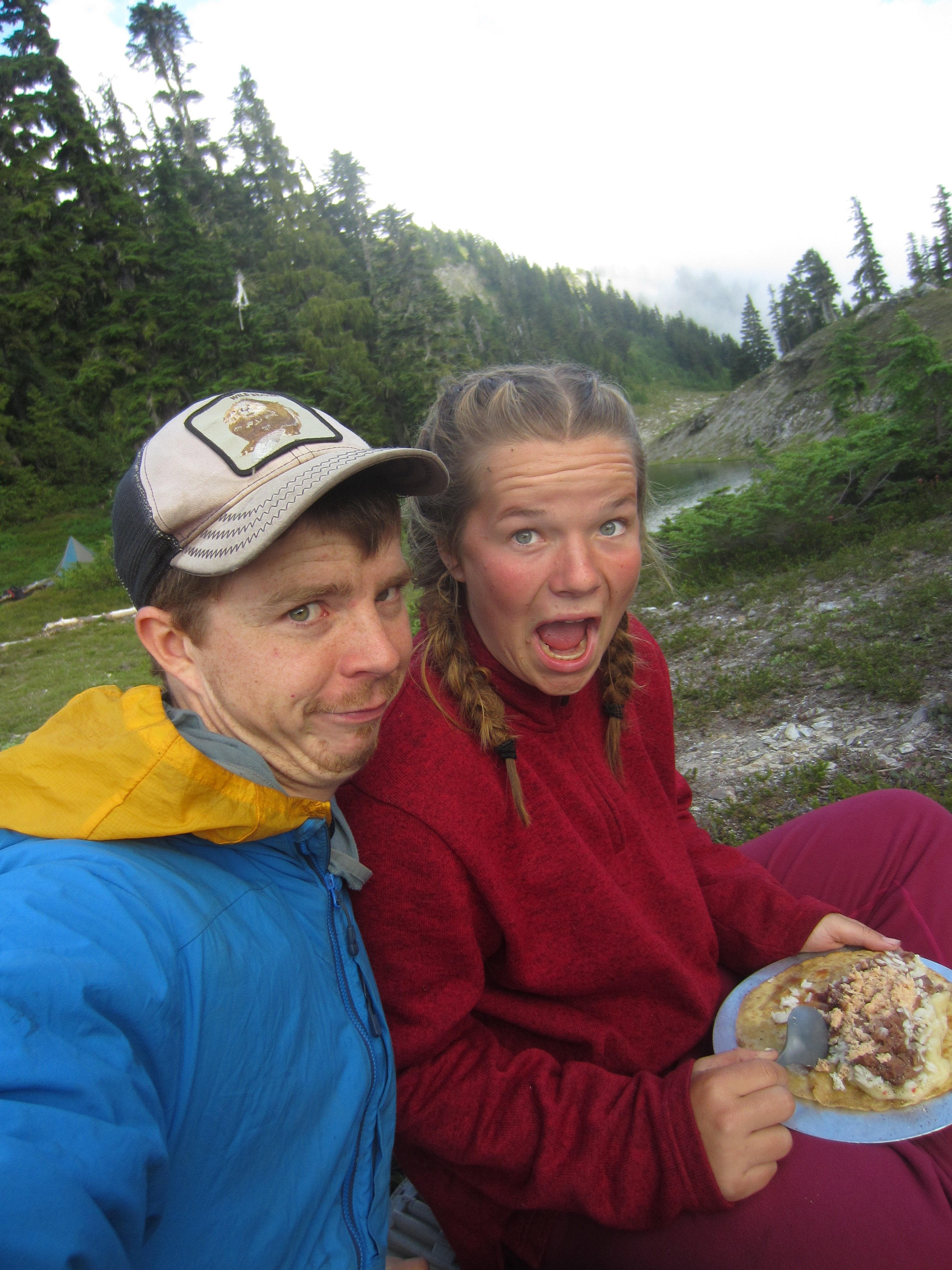 NOLS student and instructor make goofy faces for the camera while eating backcoutry burritos