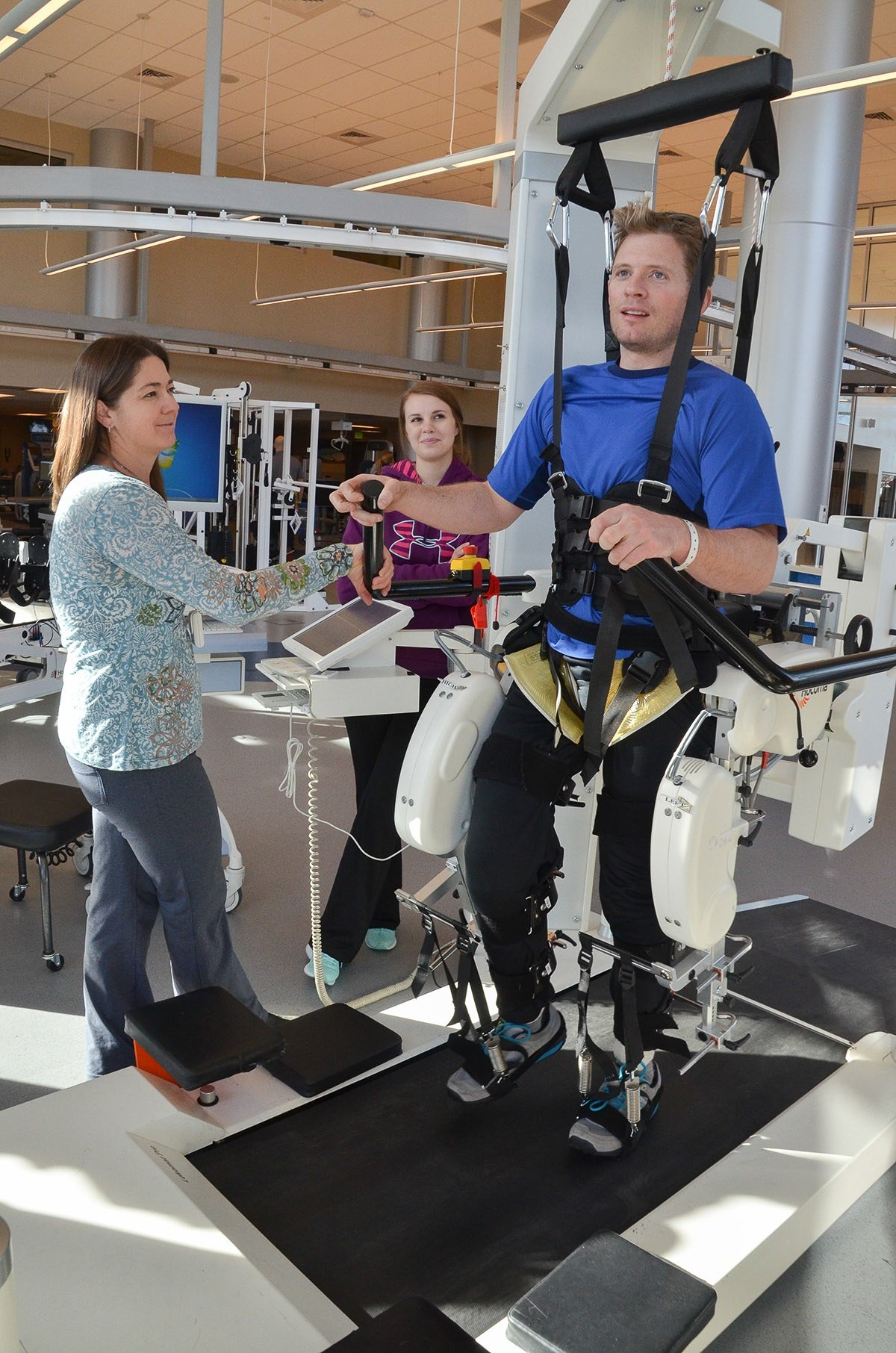 Jim Harris works with two physical therapists while strapped into an exercise machine