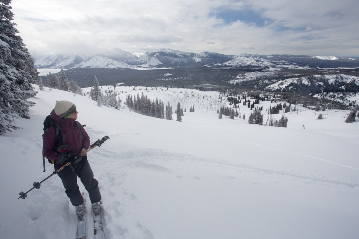 Woman pausing to rest while backcountry ski touring