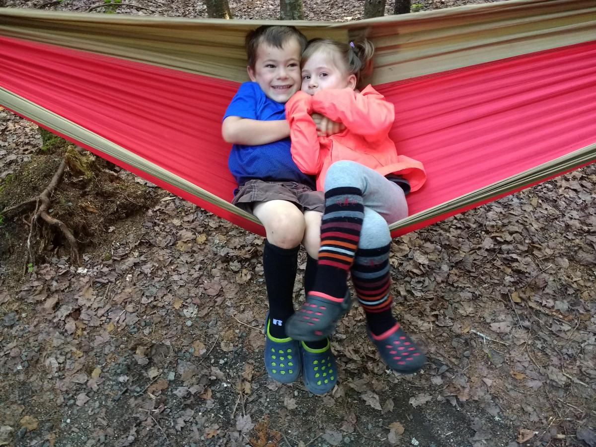 two smiling children sit together in a red and tan hammock while camping