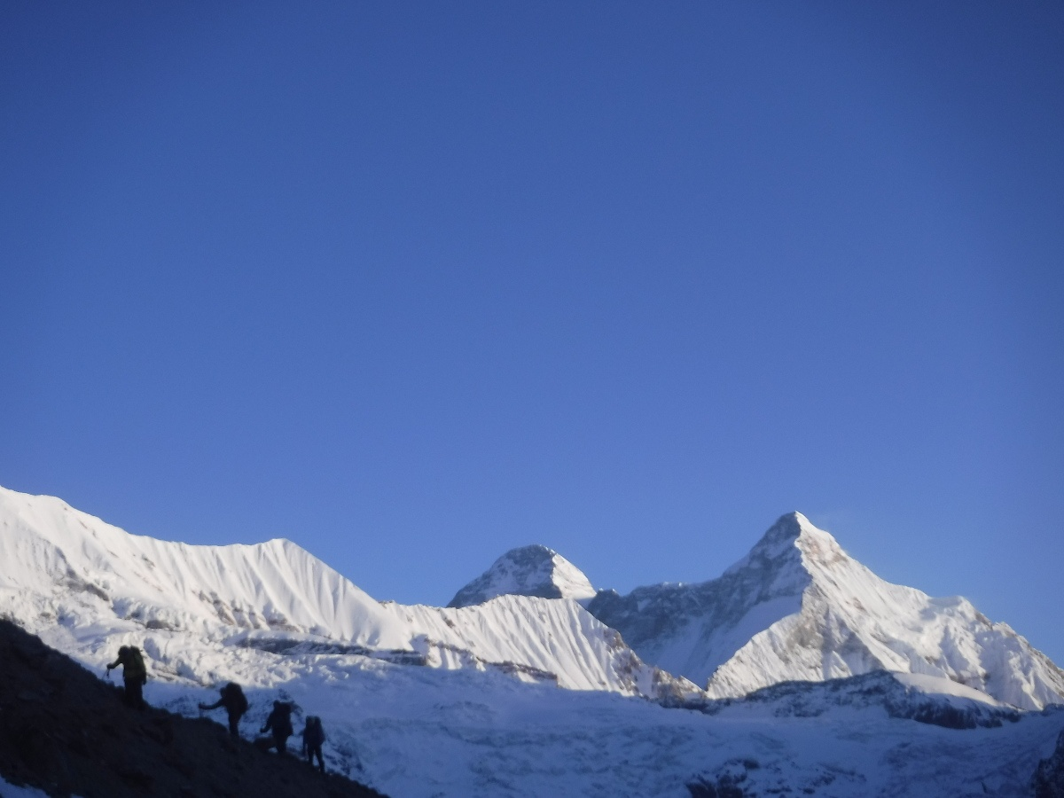 Rope team climbing a slope with Himalaya in the background