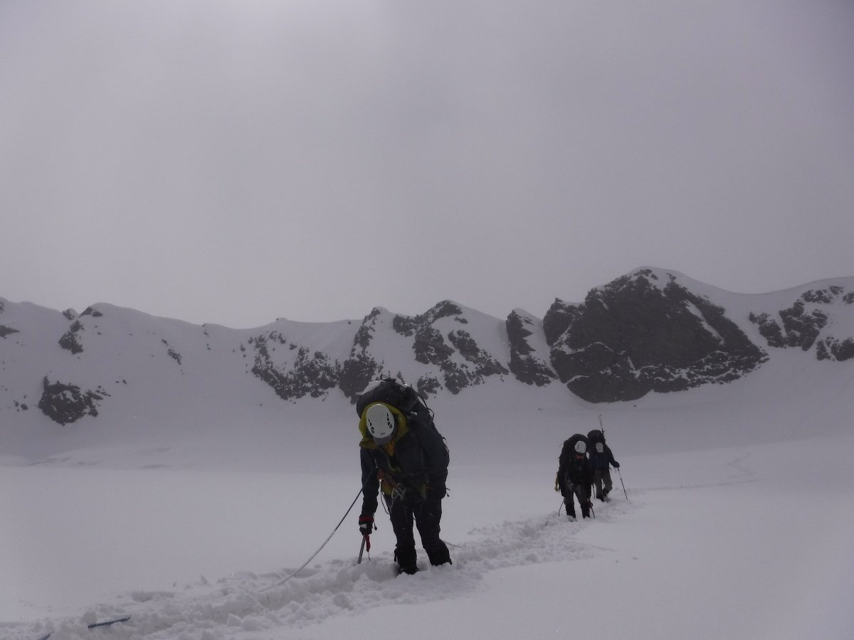 A rope team traveling through deep, heavy snow on a particularly difficult day on the Kafni Glacier
