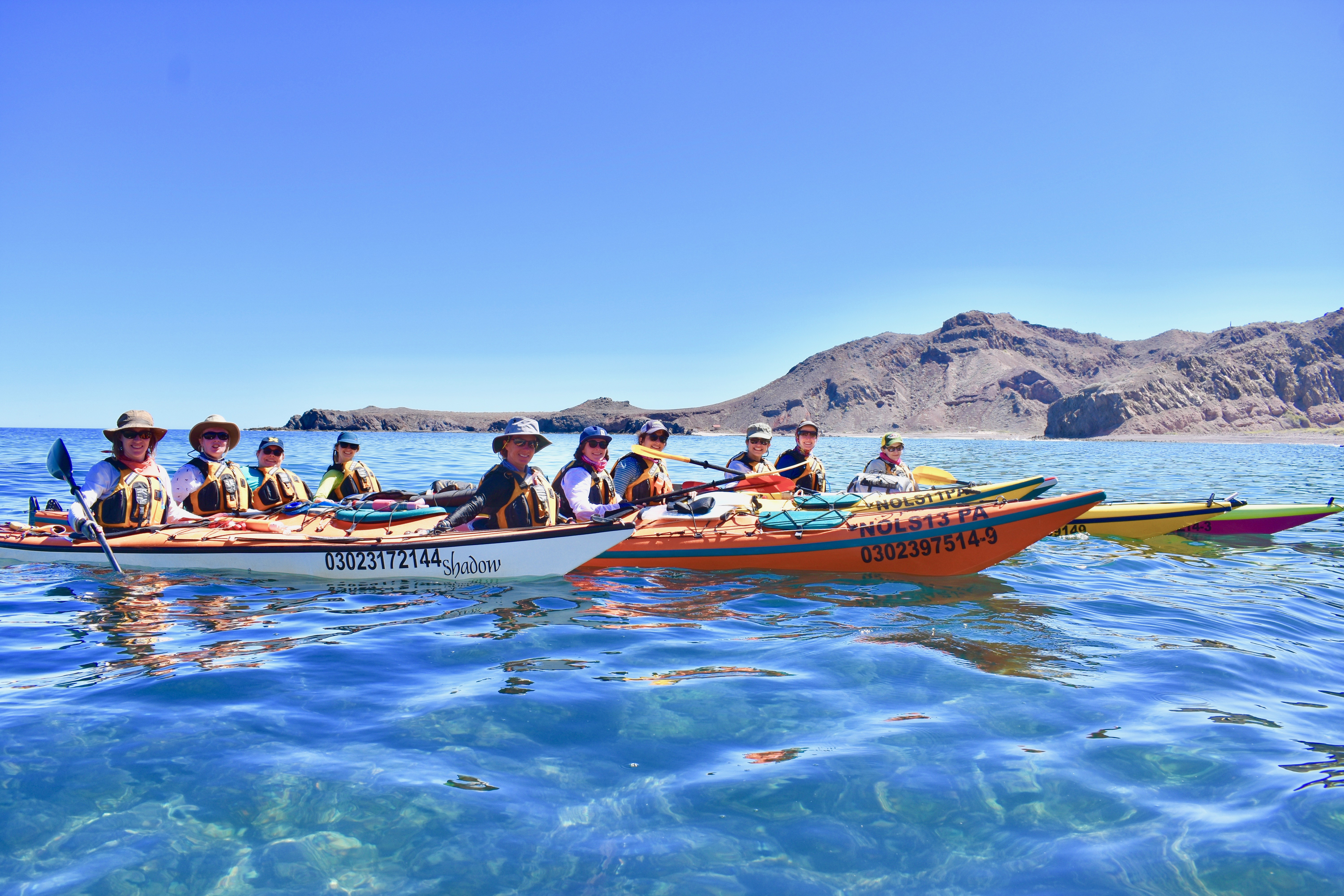 Women wearing sun hats and life preservers in colorful kayaks on clear water in Baja