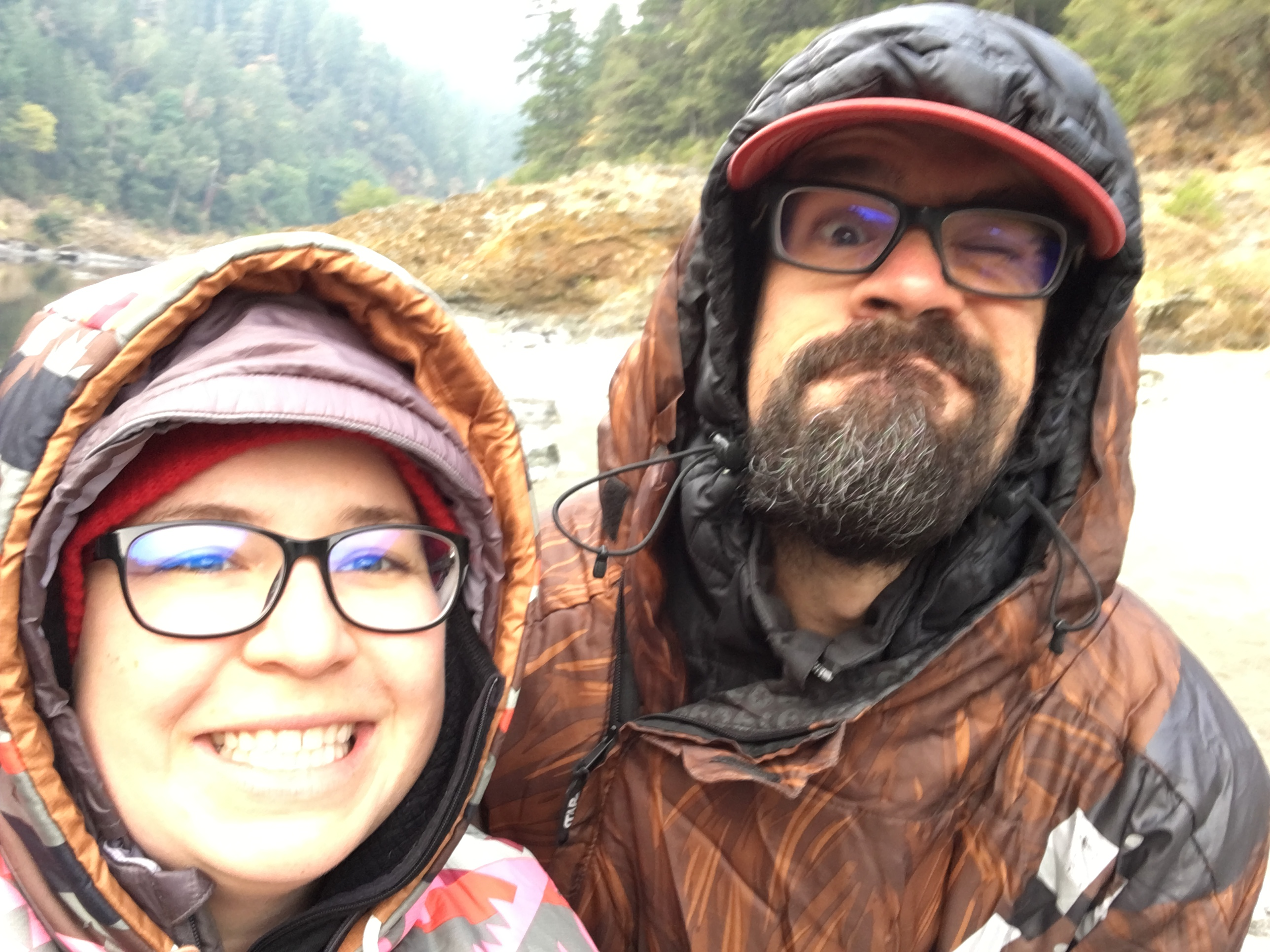Ashely Drake and her husband smile while taking a selfie photo wearing rain gear