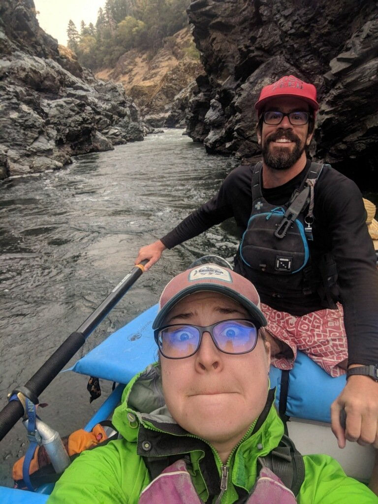 couple in a raft on the river take a selfie while making goofy faces