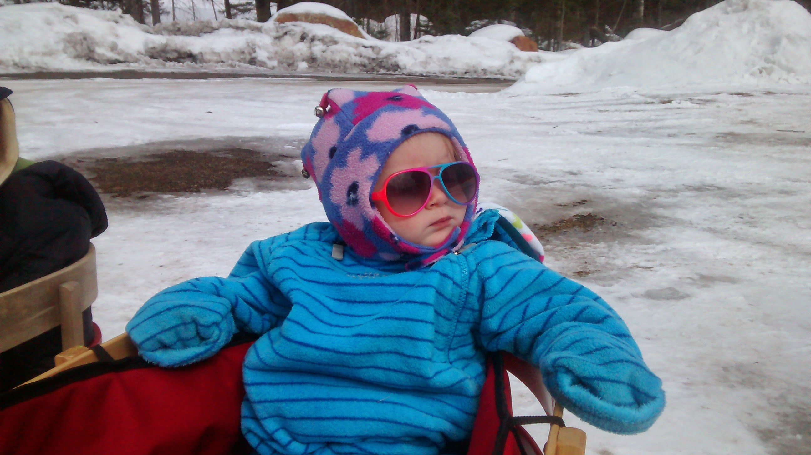 toddler in winter apparel with snow in the background and wearing sunglasses