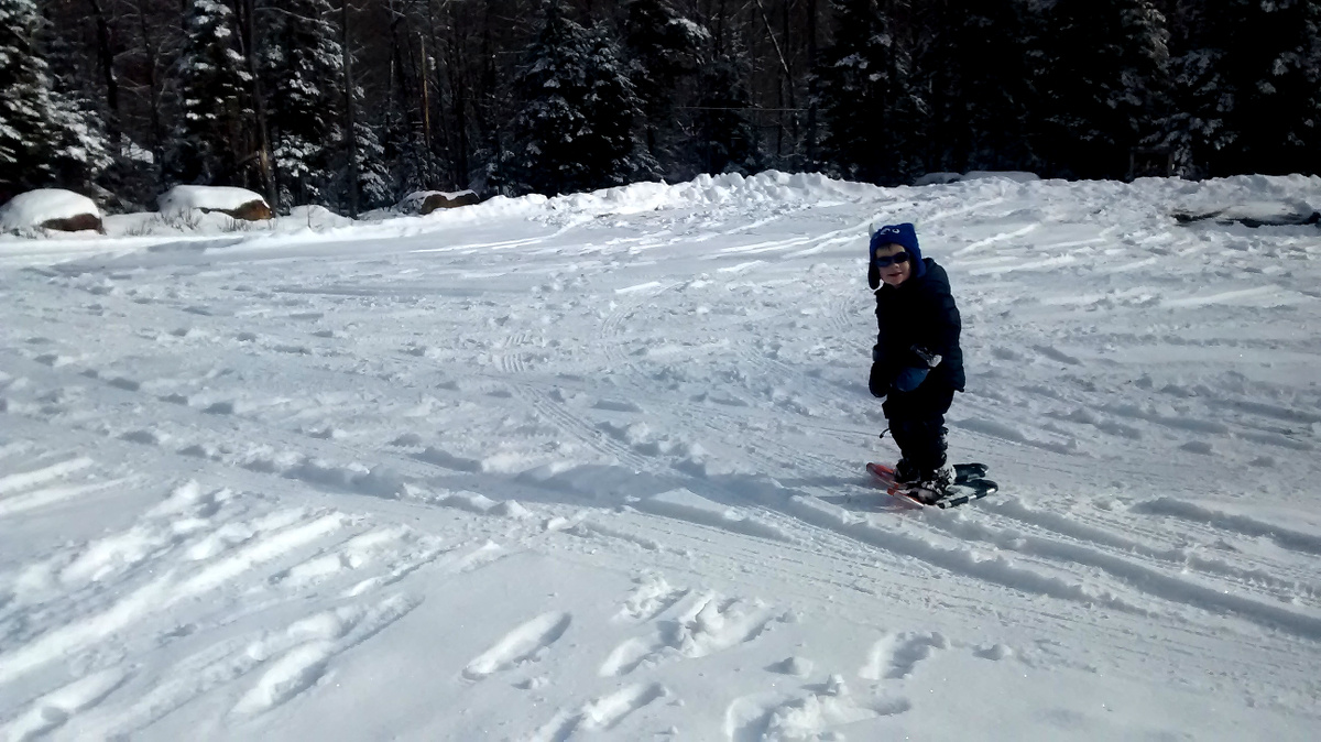Smiling child wearing winter gear, sunglasses, and snowshoes stands in a snowy parking lot facing the camera