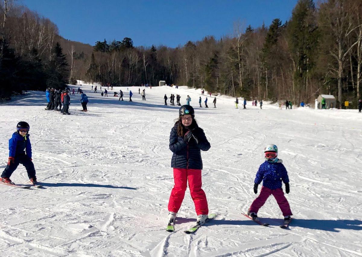 three children downhill skiing