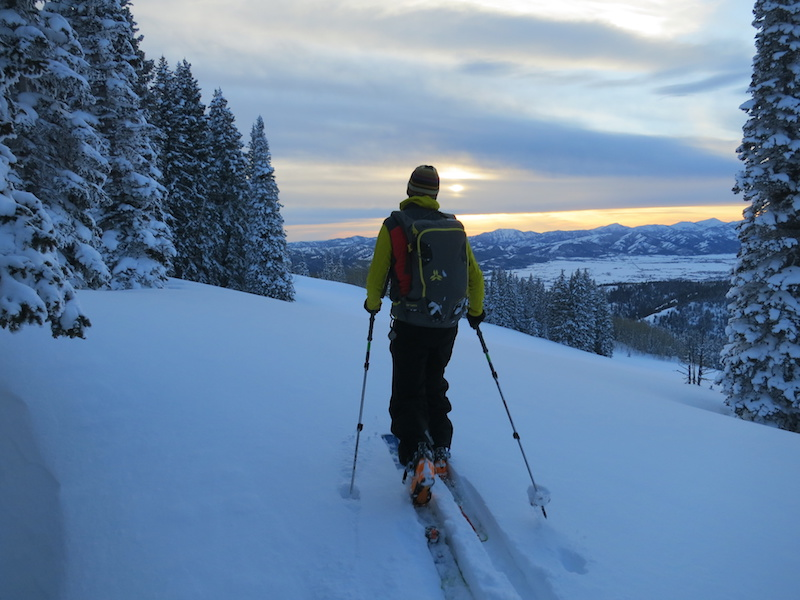 NOLS participant backcountry skis as the sun sets over snowy mountains