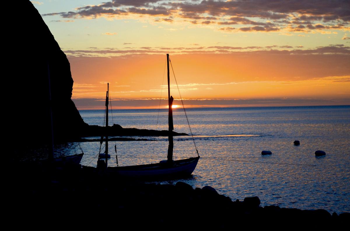 Sunrise photo of anchored longboat silhouette