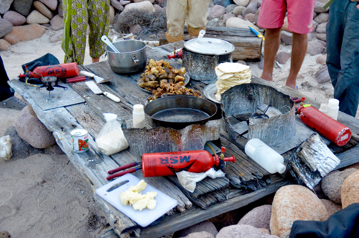 Table with cooking gear and stoves for camping