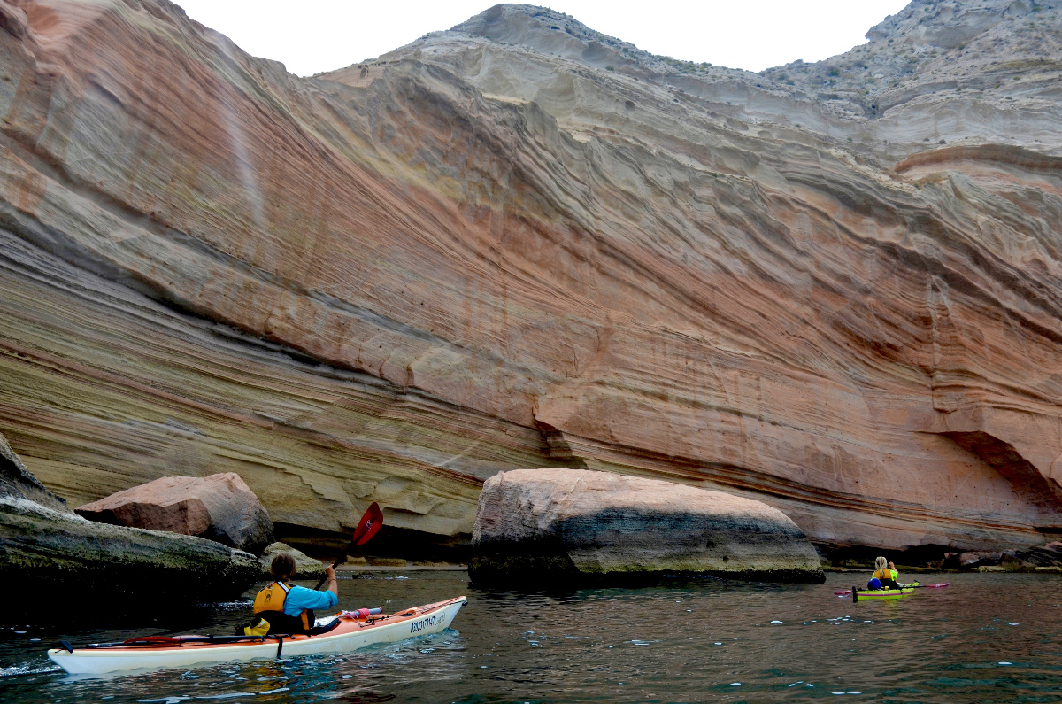 Sea kayakers paddle near wavy red sandstone wall