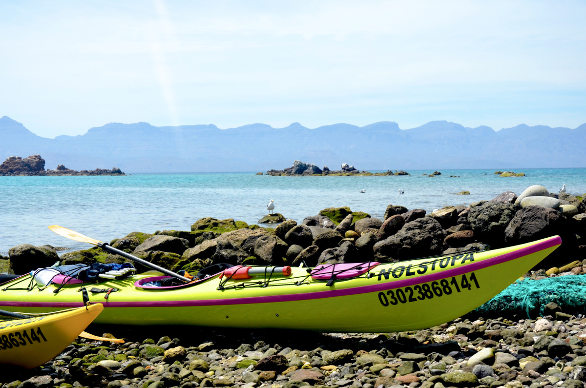 Yellow kayak beached on a rocky shore
