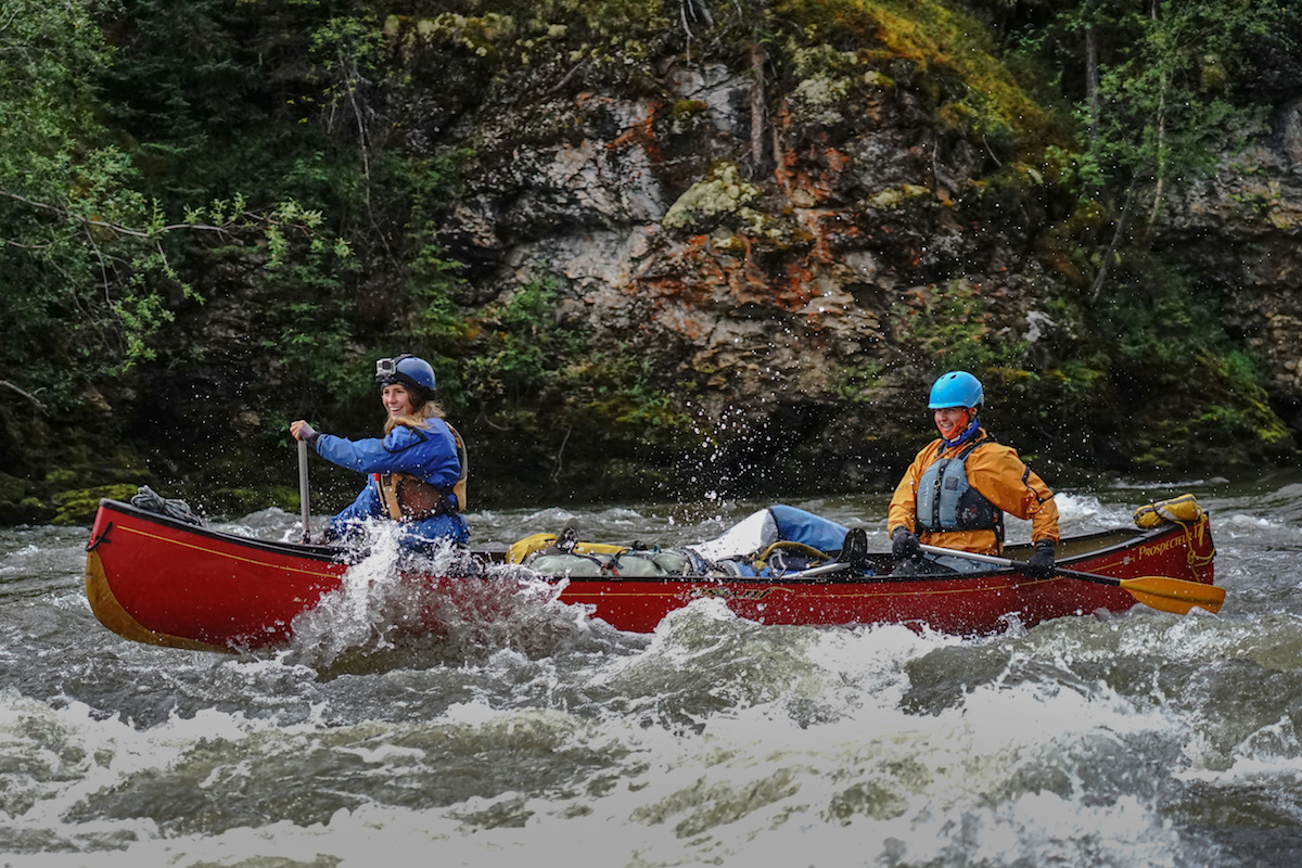 two NOLS students paddle a whitewater canoe in the Yukon
