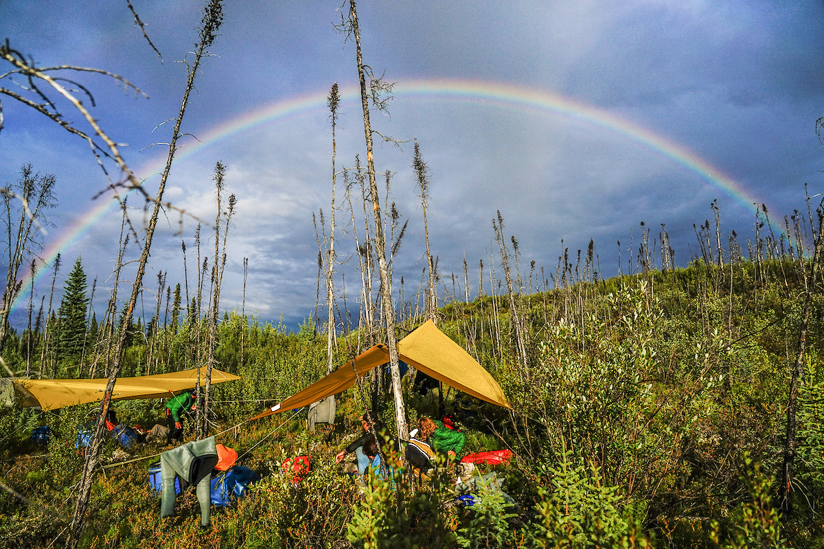rainbow above a campsite in the Yukon with tarps and clothes hung out to dry