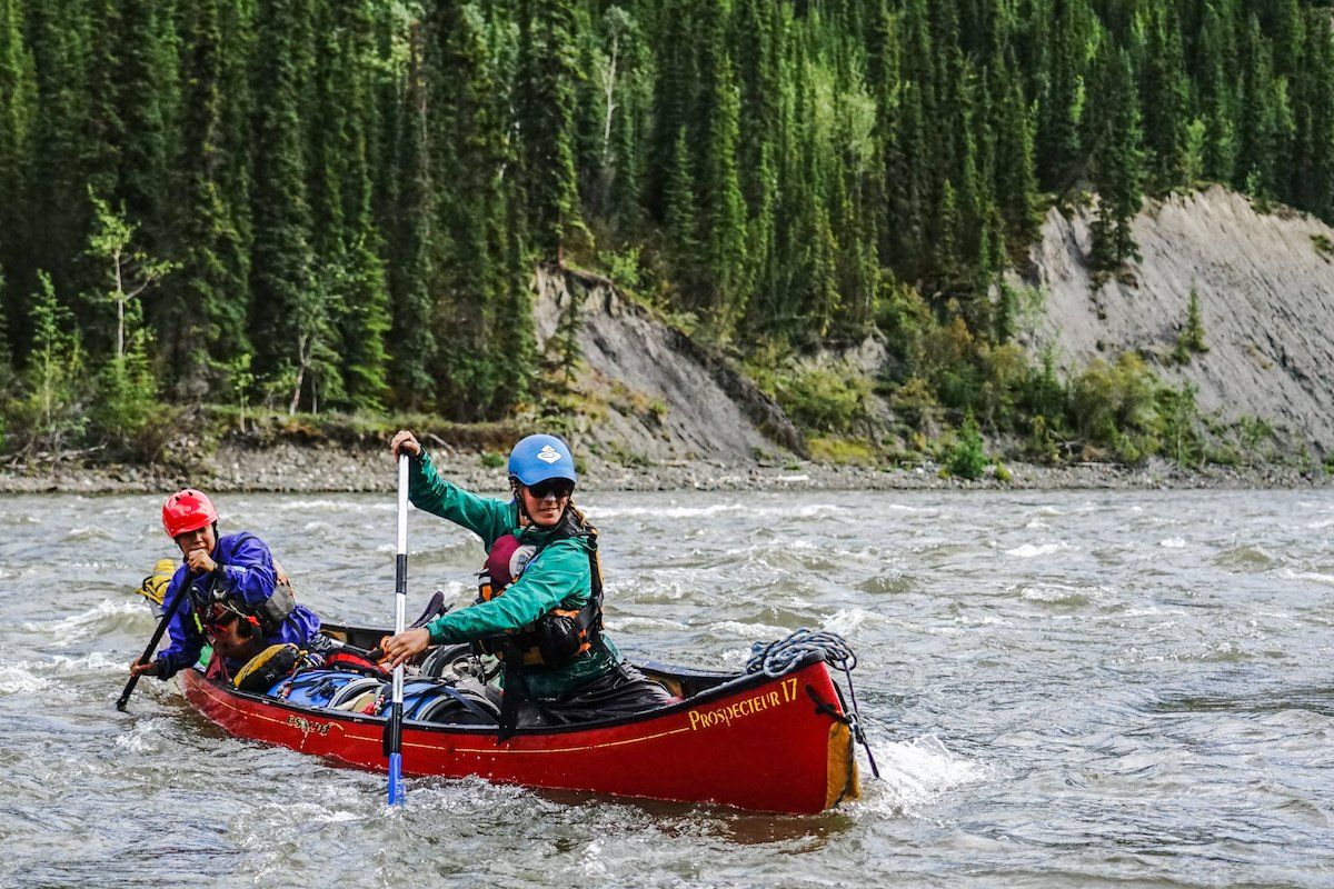 two NOLS students paddle a whitewater canoe on a river in the Yukon