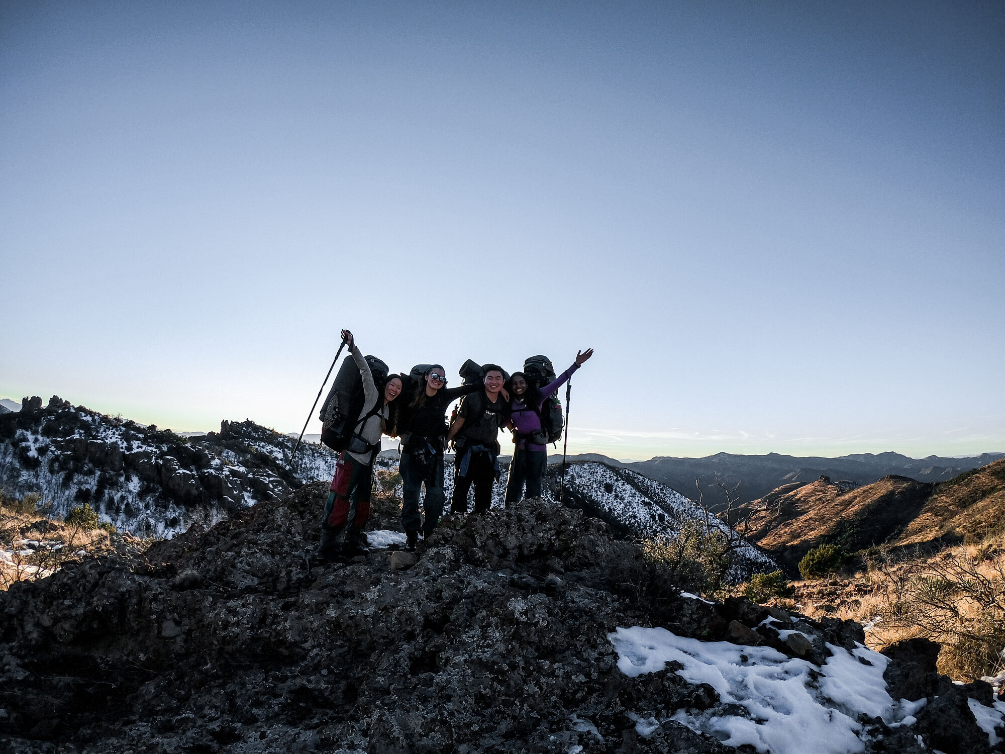 Business school students on a NOLS expedition smile for a photo on top of a snowy mound