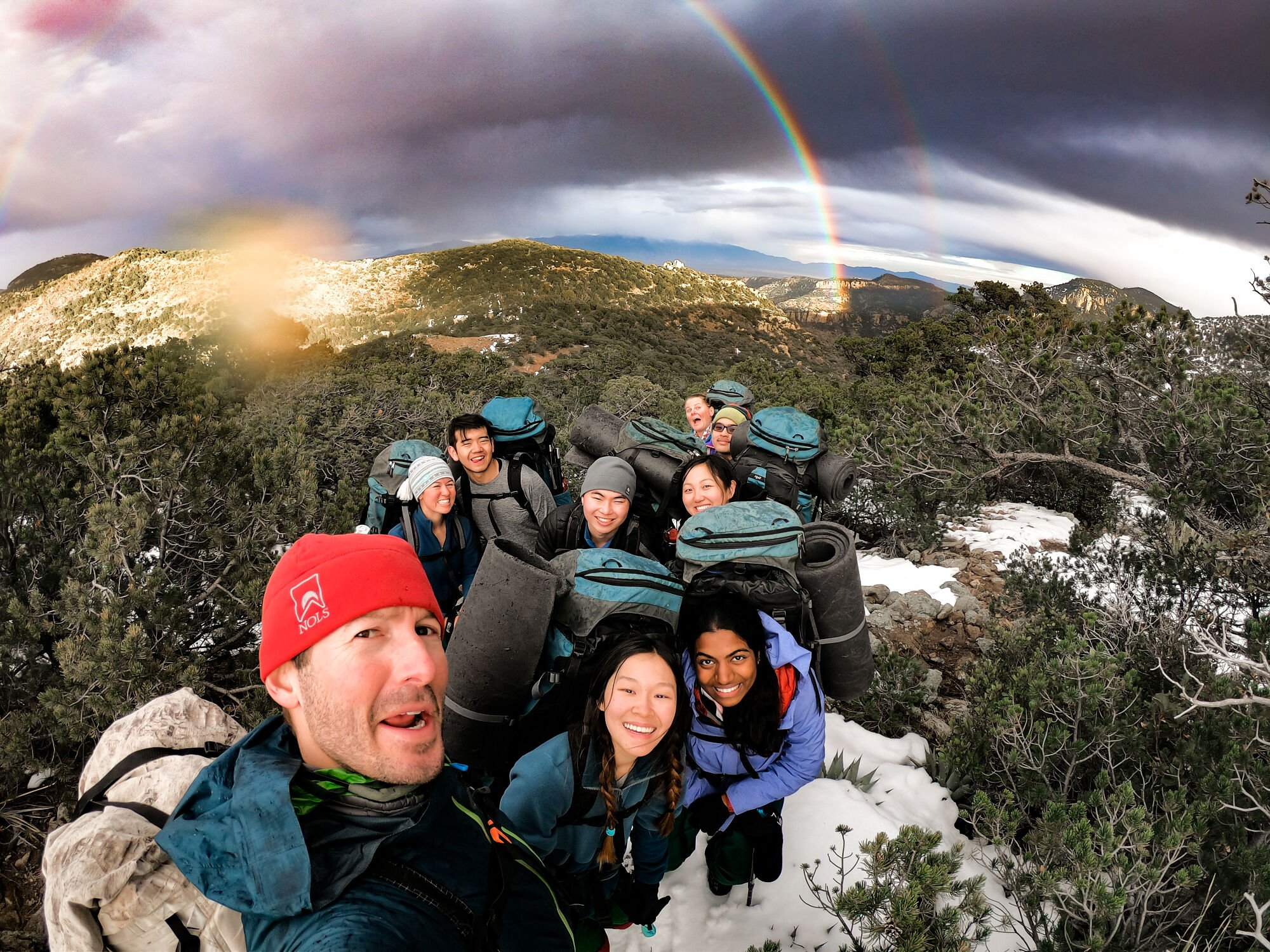 Selfie shot of a group of smiling backpackers with a rainbow in the background