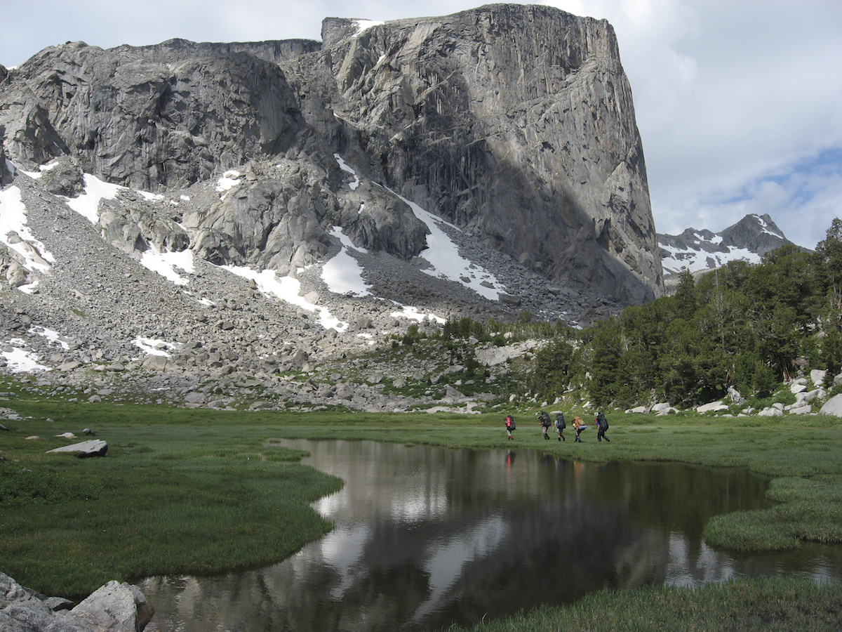 five NOLS participants hike past glassy alpine lake toward towering rocky peak