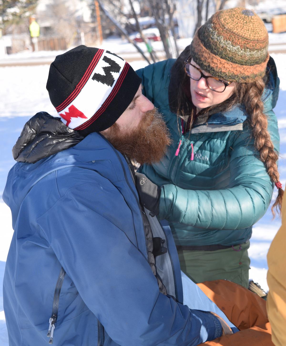 NOLS wilderness medicine students wearing winter gear practice taking a pulse