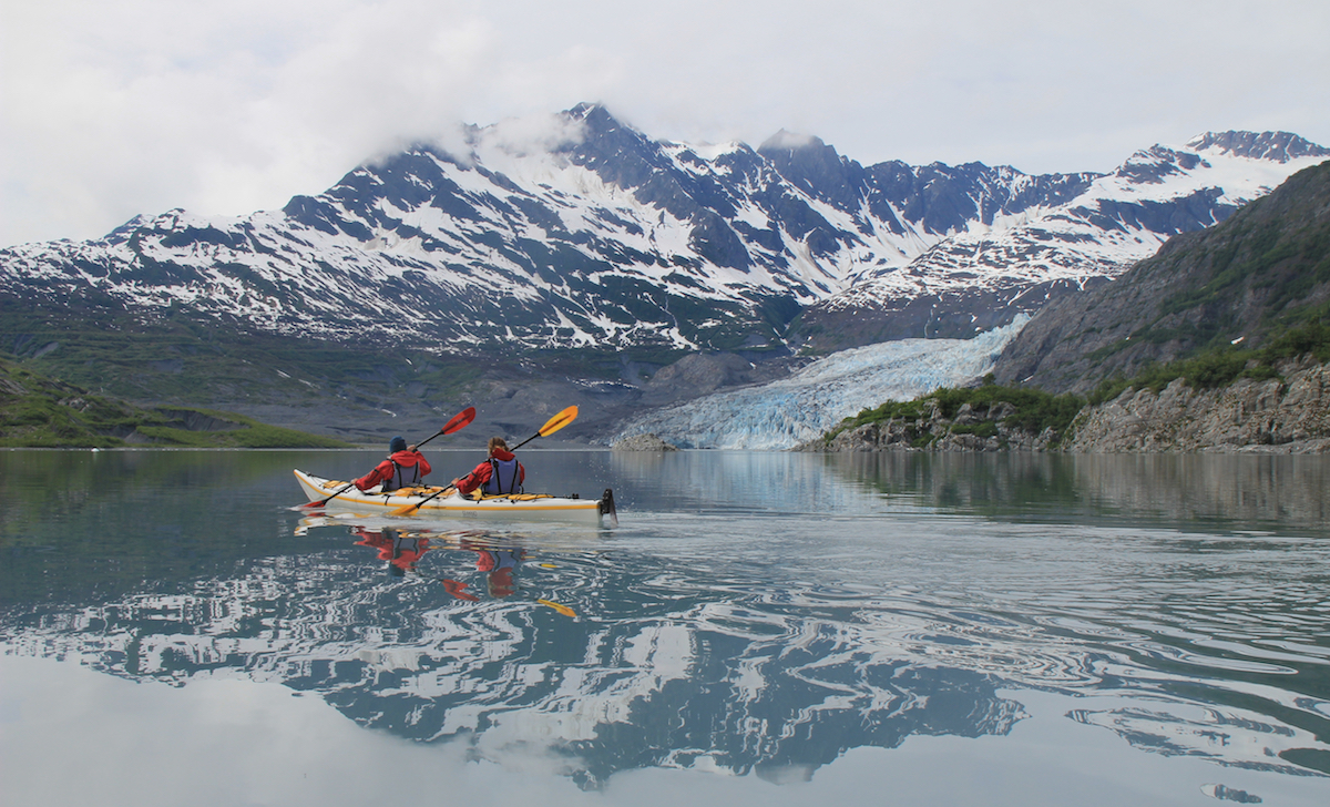 NOLS students paddle a double kayak in Prince William Sound with mountains reflected in the water
