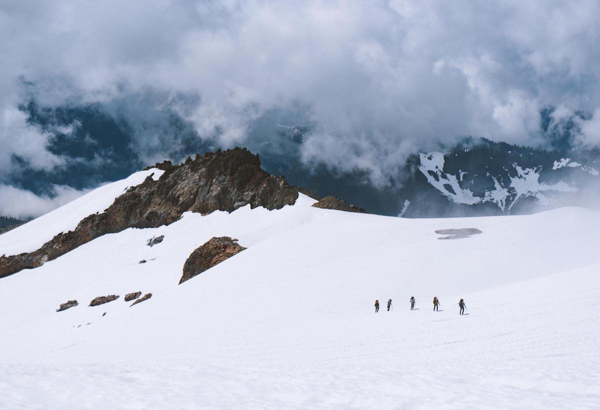 five small figures travel across a snowfield in a dramatic mountain landscape