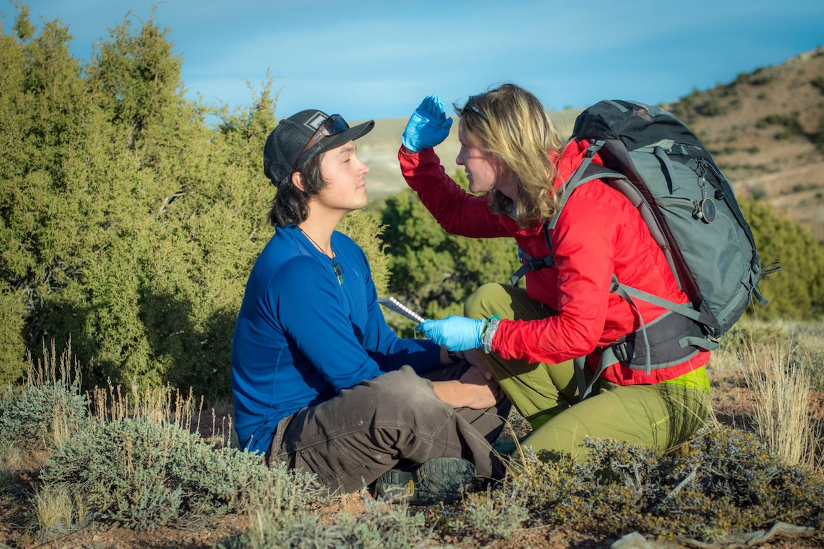 NOLS wilderness medicine student bends down beside a mock patient in the outdoors