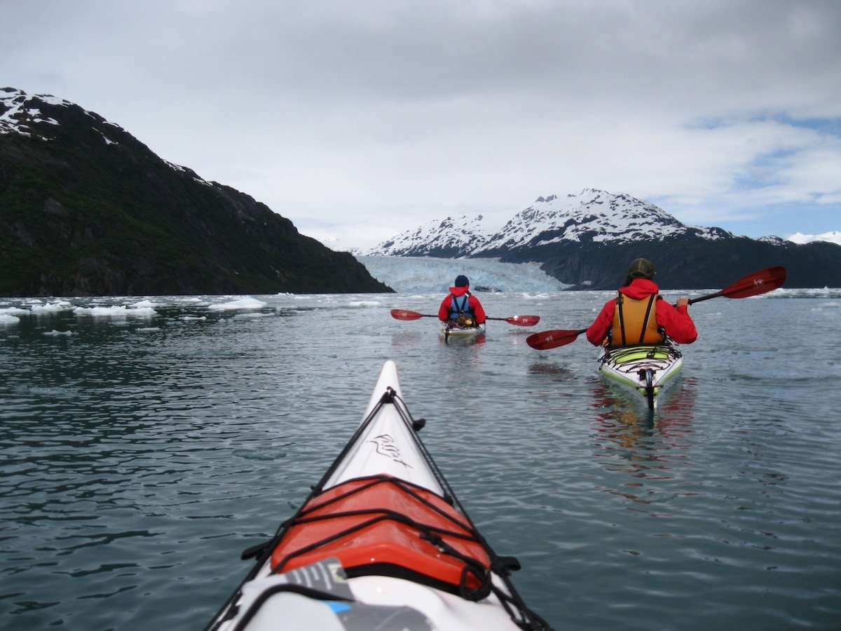 two paddlers sea kayak in Alaska on calm water with floating ice as seen over the nose of a kayak