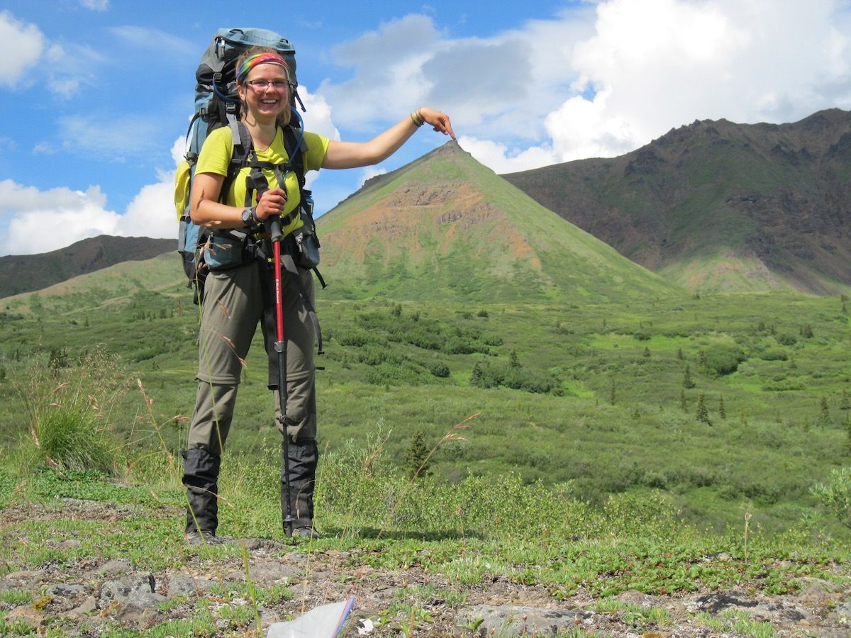 smiling female hiker wearing backpack and rainbow headband points her finger at the top of a distant mountain, creating an optical illusion