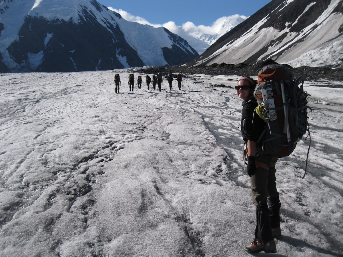smiling NOLS student wearing backpack smiles for the camera on a glacier in Alaska with other students in the distance