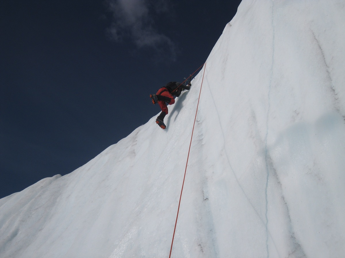 person uses crampons and rope to climb up an ice wall while mountaineering