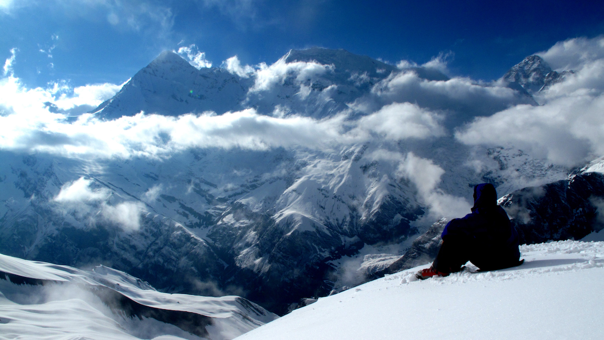 NOLS mountaineering student gazes at the snowy peaks of the Himalayas high in the clouds